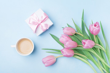 Gift box, tulip flowers and coffee on blue pastel table top view. Beautiful spring card for Womans or Mothers Day. Flat lay.