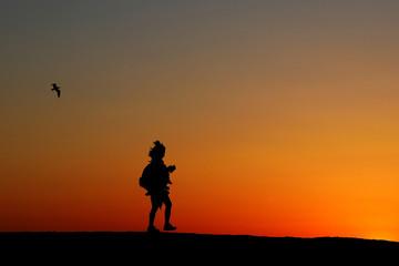 A woman is seen walking in silhouette on Venice Beach in Los Angeles