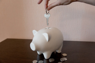Pig money box and hand with a key