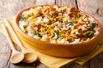 Chicken biryani with spicy spices, orange peel and cilantro close-up in a bowl. horizontal