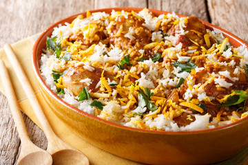 Indian pilaf biryani with chicken, onion, lemon, spices and cilantro close-up. horizontal