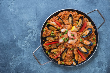 Above view of spanish paella with seafood in a frying pan, view from above on a blue stone background, copyspace