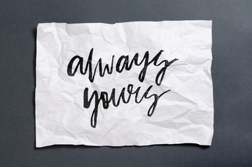 Always yours. Handwritten text on white crumpled paper. Inspirational quote.