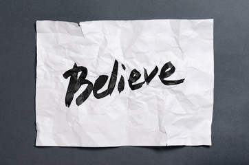 Believe. Handwritten text on white crumpled paper. Inspirational quote.