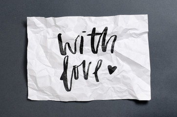 With love. Handwritten text on white crumpled paper. Inspirational quote.
