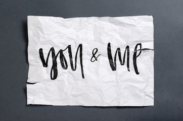 You and me. Handwritten text on white crumpled paper. Inspirational quote.