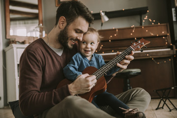 Father teaching daughter to play guitar at home