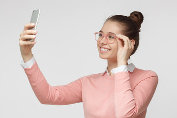 Photo of young female isolated on grey background, stretching arm with smartphone to take selfie picture to share it in social networks