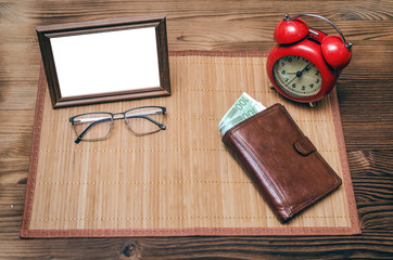 Empty photo frame with copy space, red alarm clock and wallet with money on wooden table background.