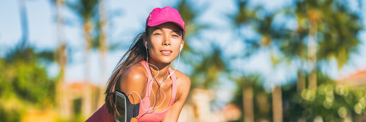 Tired runner woman running with sports cap and sport armband with earphones listening to mobile music. Active fit Asian girl resting taking a jogging break on outdoor summer lifestyle banner panorama.