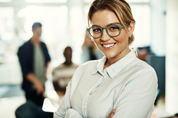 Smiling young businesswoman standing confidently in a modern office