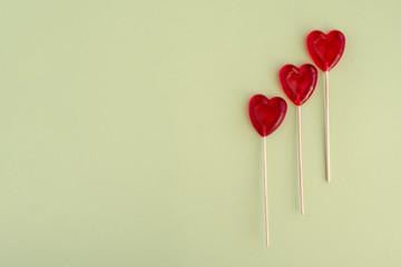 Three red heart-shaped lollipops