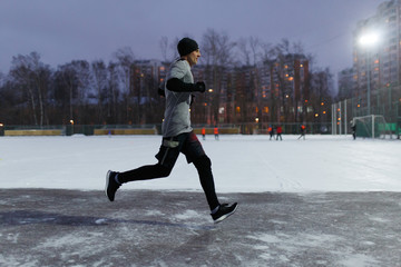 Photo of man in black sports clothes running along winter park against background of houses