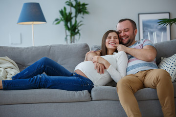 Picture of happy married couple on gray sofa