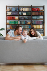 Image of happy woman and man with son on gray sofa