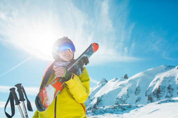 Image of smiling woman with snowboard on background of snowy hills