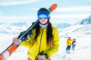 Image of girl looking at camera wearing helmet, mask with skis