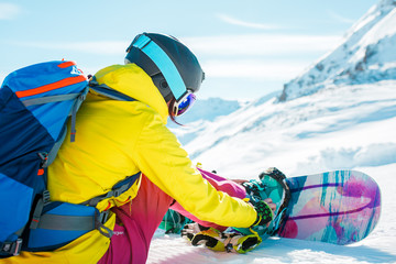 Picture of sports woman in helmet sitting on snow with snowboard