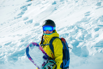 Image of smiling woman in helmet and with snowboard against background of snowy landscape