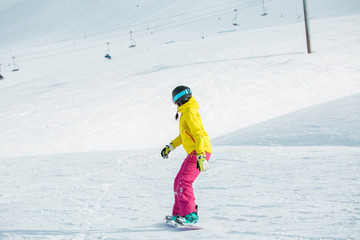 Picture of young female athlete wearing helmet in sports clothes snowboarding