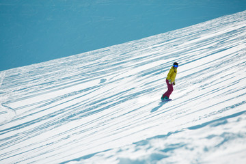 Picture of sports girl wearing helmet and mask, snowboarding from mountain slope