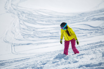 Photo of brunette wearing helmet and mask in sports clothes snowboarding from snowy mountain slope