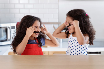 Little girls looking at each other laughing making mustache with their hair