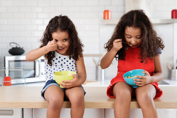 Little girls sitting on kitchen counter eating cereal bowls