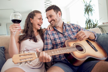 Young man play the guitar in the room for his girlfriend.