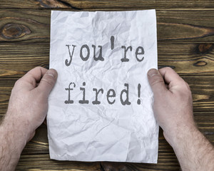 you're fired! text on crumpled paper in the hands of a businessman. unemployed, dismissal, fax.