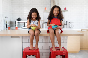 happy little girls sitting on kitchen counter having breakfast