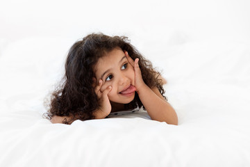 Funny little girl lying on stomach on bed making funny face
