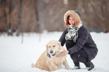 Picture of smiling woman squatting next to labrador with toy in teeth in winter park
