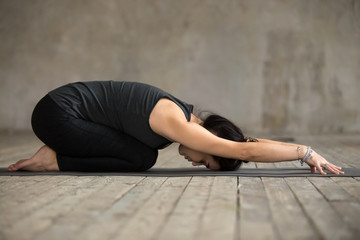 Young woman practicing yoga, doing Child exercise, Balasana pose, working out, wearing sportswear, black pants and top, indoor full length, gray wall in yoga studio