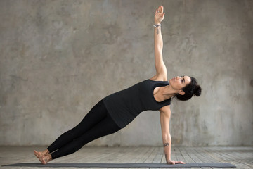 Young woman practicing yoga, doing Vasisthasana exercise, Side Plank pose, working out, wearing sportswear, black pants and top, indoor full length, gray wall in yoga studio