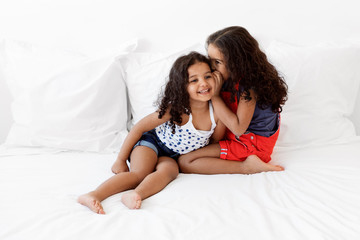 Little girls smiling and sharing secrets on bed