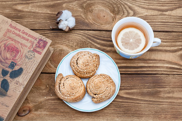Tea with lemon, homemade cookies and a book on a wooden table.