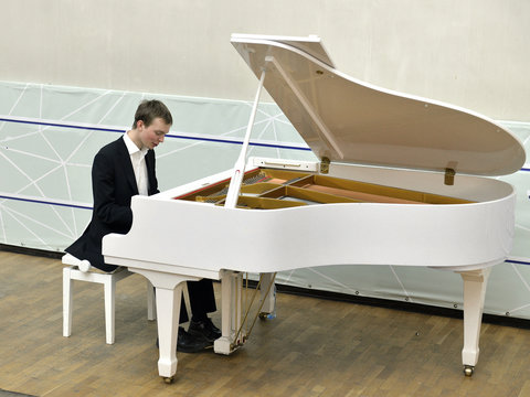 Young handsome man with white grand piano