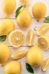 Wall Mural - Ripe lemons and lemon leaves on wooden background. Top view.