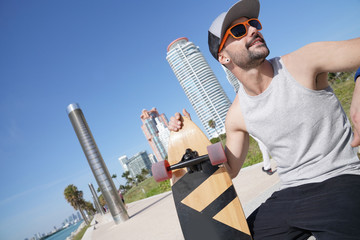 Skateboarder relaxing by Miami beach waterfront
