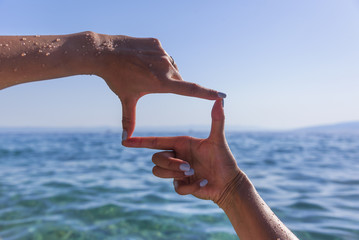 Hands show a square against the sea.