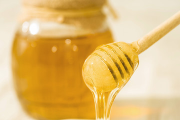 A honey spoon against the background of a jar filled with honey