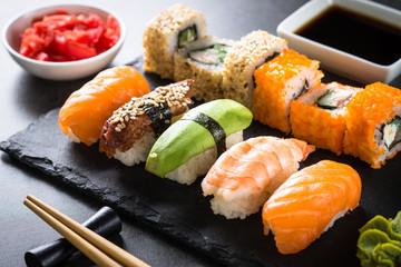 Aluminium Prints Sushi bar Sushi and sushi roll set on black stone table.