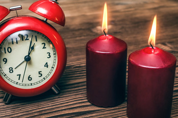 Red alarm clock and two burning candles on wooden desk table background.
