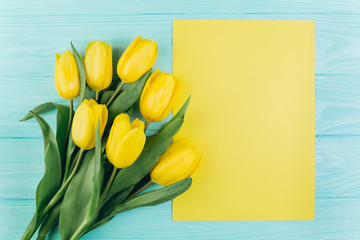 Yellow tulips and postcard on a blue wooden background, copy space and flat lay. Mother's Day concept.