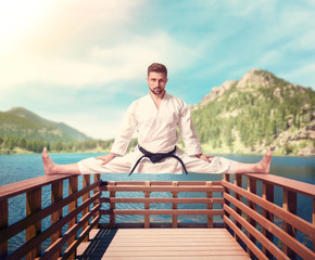 Martial arts master, stretching exercise on pier