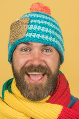 Cheerful man with beard and mustache wearing fashionable scarf and hat. Male winter fashion. Handsome man in hat and scarf. Attractive bearded man in warm knitted hat and scarf. Closeup portrait.