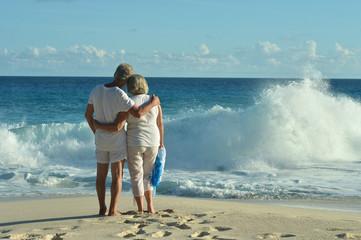 elderly couple standing on sandy beach