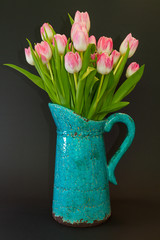 Pink tulips in a turquoise vase on a dark background