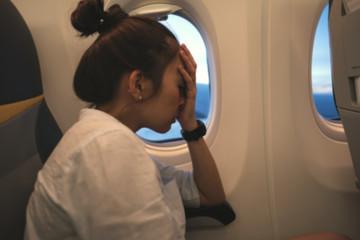 blur woman sad on a plane beside windows